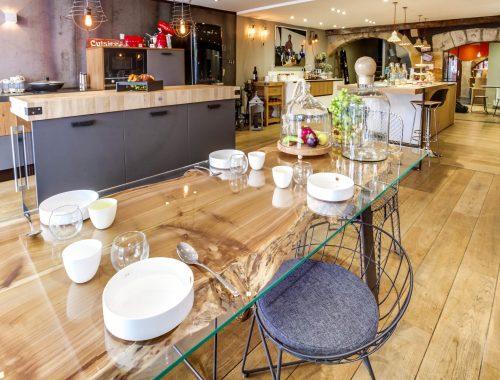Univers cuisines chez Bulles Cuisines à Lyon. Showroom entièrement relooké. Table en verre, avec un jeu de transparence sur la base en bois massif à la découpe naturelle. Chaise métallique noire.