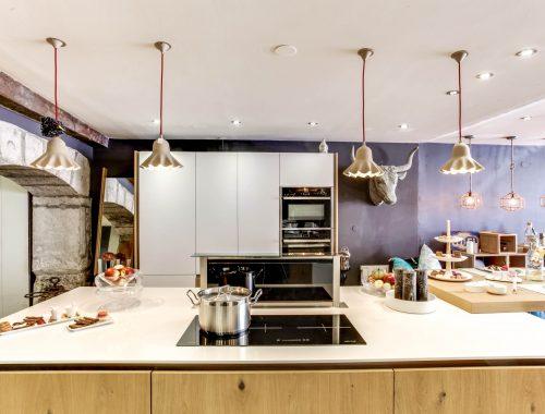 Univers cuisines chez Bulles Cuisines à Lyon. Showroom entièrement relooké. Cuisine blanche et bois, pour un effet scandinave moderne. Déco bestiale avec le trophée décoratif en forme de tête de buffle.