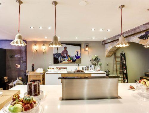 Univers cuisines dans le showroom revisité de Bulles Cuisines à Lyon. Zoom sur une hotte design inox escamotable, intégrée au plan de travail de l'îlot central.
