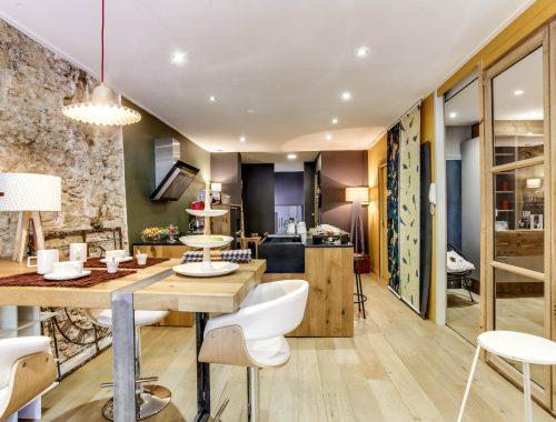 Univers Cuisines au showroom Bulles Cuisines, Quai Saint Antoine à Lyon, récemment rénové. Zoom sur une cuisine avec îlot central bois et gris anthracite.