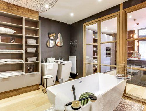 Univers salle de bain chez Bulles Cuisines à Lyon. Salle de bain avec baignoire blanche, dressing et 2 meubles vasques XXL au design contemporain. Jeu de 3 miroirs forme goutte pour un rendu zen et aérien.