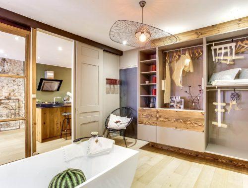Univers salle de bain chez Bulles Cuisines à Lyon. Salle de bain avec baignoire blanche, dressing et 2 meubles vasques XXL au design contemporain. Lustre métal XXL noir.