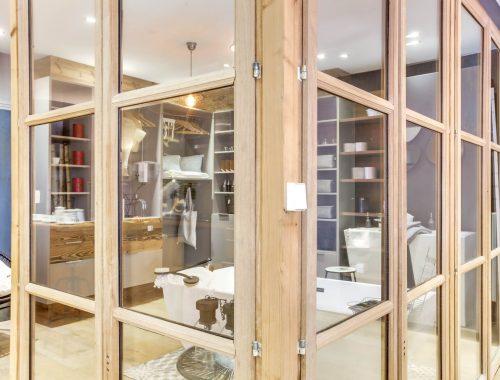 Univers salle de bain chez Bulles Cuisines à Lyon. Vue à travers une cloison vitrée : salle de bain avec baignoire, dressing et 2 meubles vasques XXL au design contemporain.