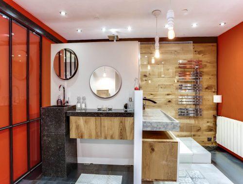 Univers salle de bain chez Bulles Cuisines à Lyon. Salle d'eau avec douche italienne, paroi vitrée, mur effet bois, sèche serviette chromé effet miroir. Meuble bois et blanc laqué, meuble vasque contemporain en pierre anthracite. Verrière type atelier et pan de mur orange vitaminé.