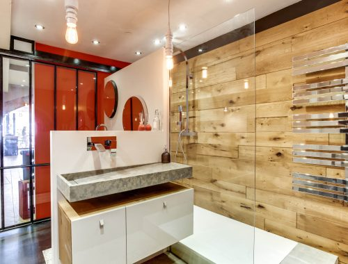 Univers salle de bain chez Bulles Cuisines à Lyon. Salle d'eau avec douche italienne, paroi vitrée, mur effet bois, sèche serviette chromé effet miroir. Meuble bois et blanc laqué, double vasque pierre. Verrière type atelier et pan de mur orange vitaminé.