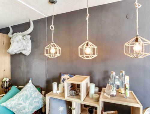 Sélection d'objets de décoration au showroom Bulles Cuisines, Quai Saint Antoine à Lyon. Mur gris, trophée décoratif tête d'animal, lustres ficelle suspendus, niches en bois.