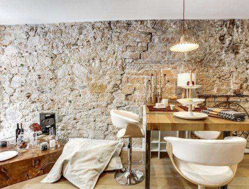 Découvrez les objets déco et arts de la table au showroom Bulles Cuisines à Lyon, fraîchement rénové. Table bois avec pied en métal, tabouret bois avec revêtement blanc tendance scandinave, mur en pierres apparentes. Table basse en bois massif pour un effet rustique moderne.