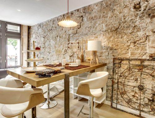 Découvrez les objets déco et arts de la table au showroom Bulles Cuisines à Lyon, fraîchement rénové. Table bois avec pied en métal, tabouret bois avec revêtement blanc tendance scandinave, mur en pierres apparentes.